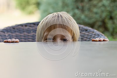 Little boy hiding behind the table