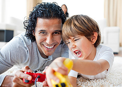 Little boy and his father playing video games