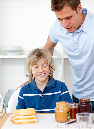 Little boy and his father preparing breakfast