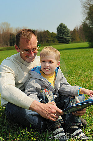 Little boy and his father are reading a book