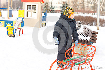 Little boy with his sled in winter snow