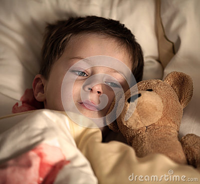 Little boy and his teddy bear are going to sleep