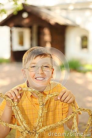 Little boy hold braided straw in hands