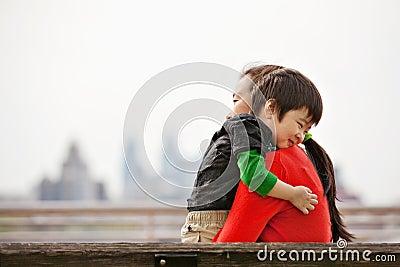 Little boy hugging mommy on bench