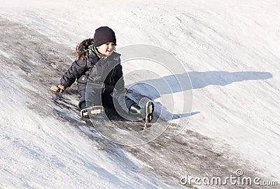 Little boy on ice hill
