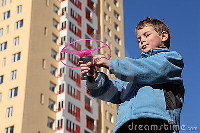 Little boy in jacket plays with pink propeller