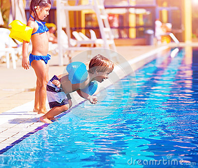 Little boy jumping into the pool
