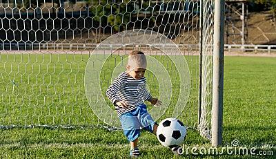 Little boy kicking a ball
