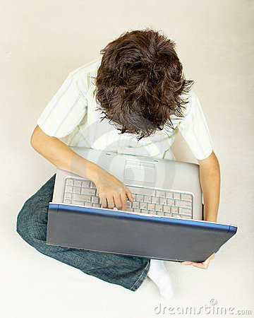 Little boy with laptop working on the floor