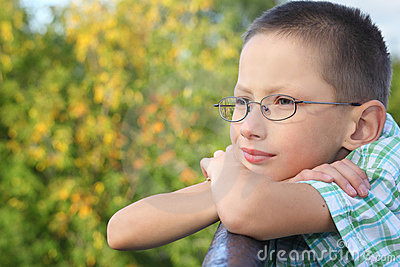 Little boy is lean elbow on bridge fence