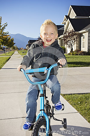 Little boy learning to ride a bike with training wheels
