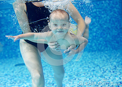 Little boy learning to swim in a swimming pool