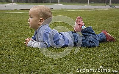 The little boy lies on the football field.