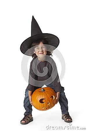 Little boy is lifting a Halloween pumkin