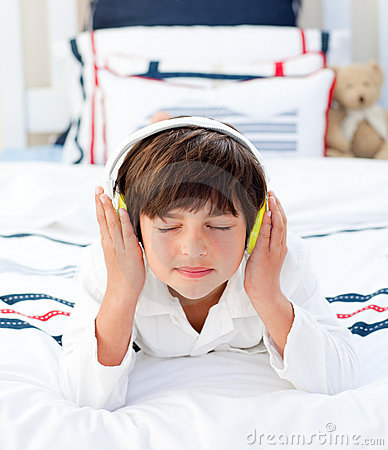Little boy listening music with headphones on