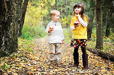 Little boy and little girl eating apples in forest