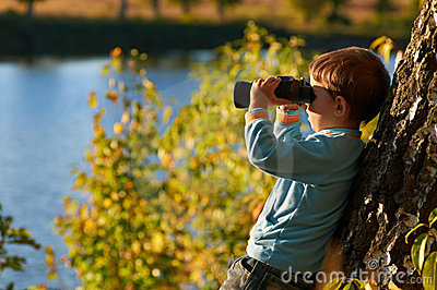 Little boy looking through binocular