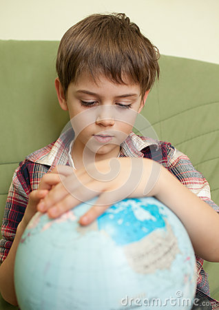Little boy looking at globe