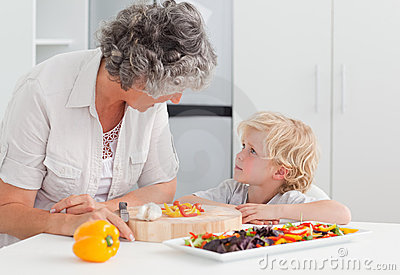 Little boy looking at his grandmother cooking