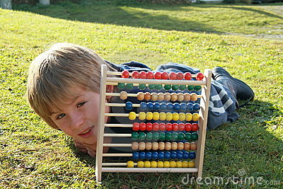 Little boy lying behind an abacus
