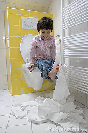 Little boy makes a mess with toilet paper in the
