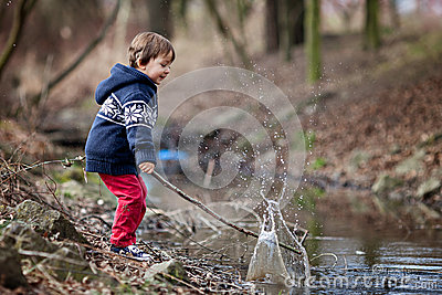 Little boy, making big splash on a pond