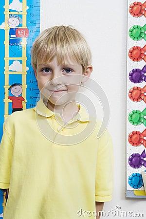 Little Boy Measuring Height In Classroom