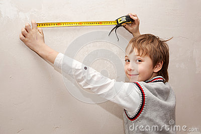 The little boy measuring tape something