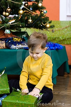 Little boy opening Chrismas present