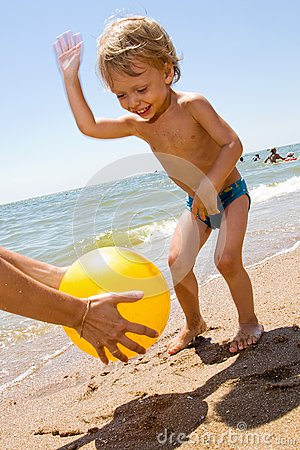 Little boy plas ball at the seaside