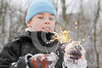 Little boy play with sparkler in forest