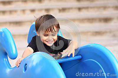 Little boy on playground equipment