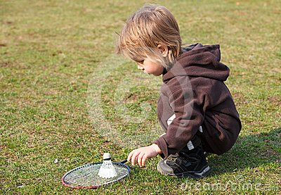 Little boy playing badminton outdoors