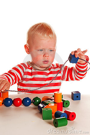 Little boy playing with beads