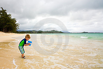 Little Boy Playing with a Bucket on the Beach
