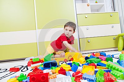 Little boy playing with his plastic cubes