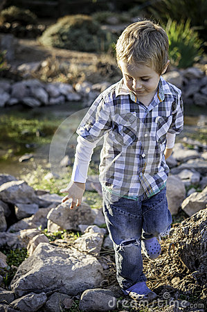 Little boy playing at the river