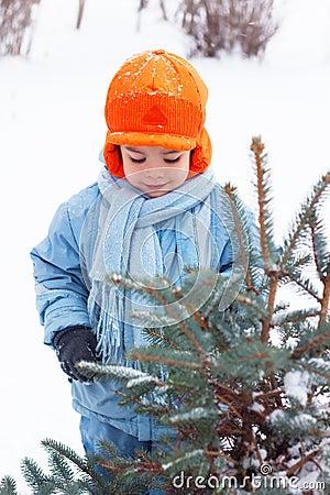 Little boy playing snowballs, snowman sculpts