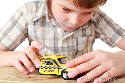 Little boy playing with toy yellow Taxi