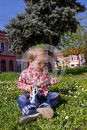 Free Little Boy Playing With Grass And Toy Police Car In Nature Royalty Free Stock Images - 110242709