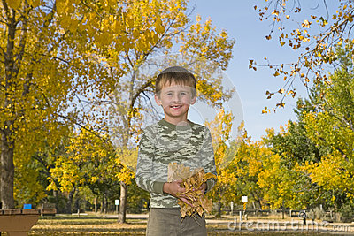 Little boy plays with colorful leaves in air