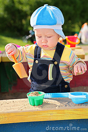 Little boy plays in sandbox