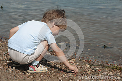Little boy plays with stones