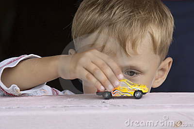 Little boy plays a toy car