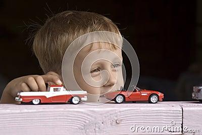 Little boy plays a toy car