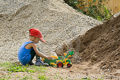 Little boy plays with a toy tractor