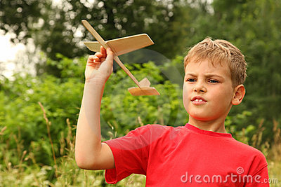 Little boy plays with wooden airplane on nature