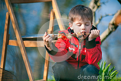 Little boy with pleasure eats grilled vegetables