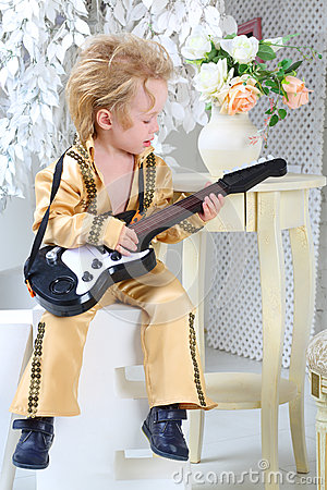 Little boy in pop retro suit playing the guitar