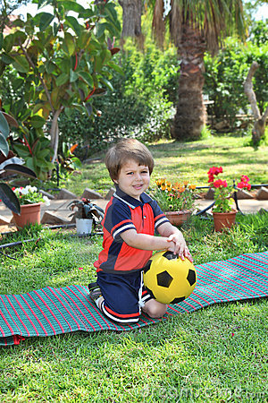 A little boy poses on a green lawn